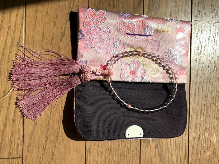 女性の数珠とピンクの数珠入れ